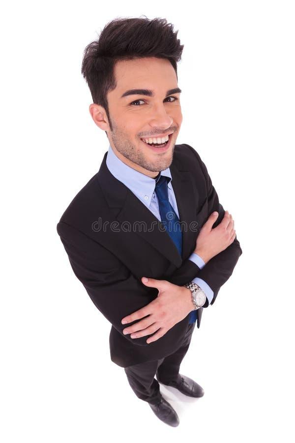 Immagine grandangolare di un uomo d'affari sorridente con le mani attraversate fotografia stock
