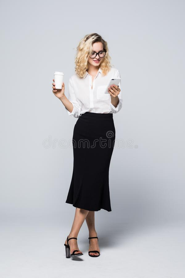Immagine integrale della donna graziosa di affari nell'usura convenzionale che sta e che per mezzo del telefono cellulare con caf immagini stock libere da diritti