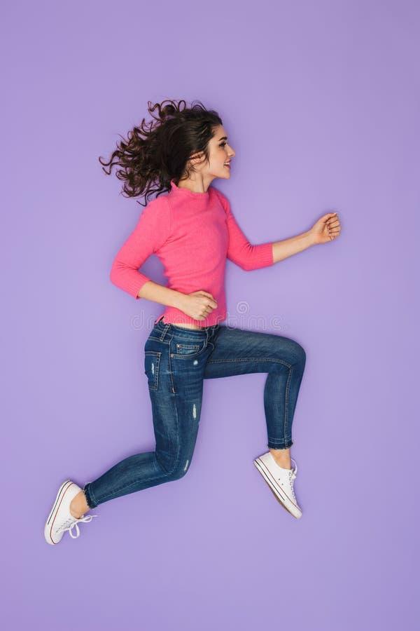 Immagine integrale della giovane donna 20s in abbigliamento casuale che sorride e che corre da parte immagini stock libere da diritti