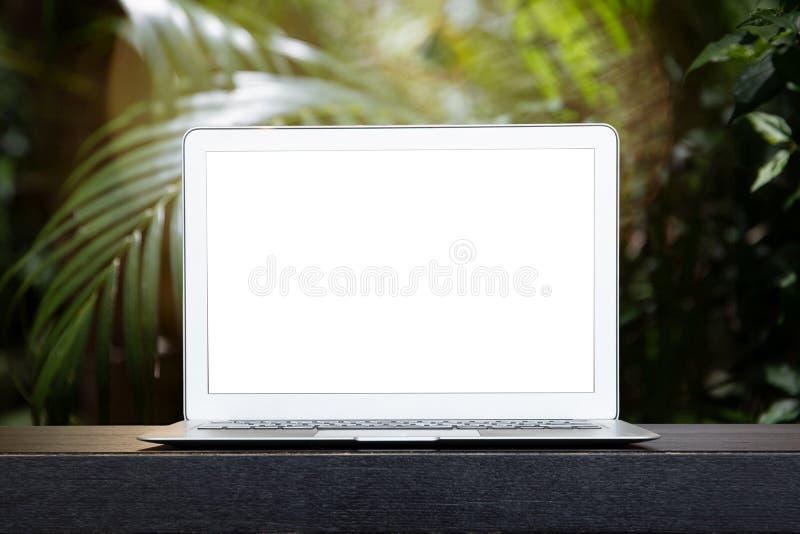 Immagine isolata del modello del computer portatile con sfuocatura sulle foglie verdi del plam o dell'albero in foresta tropicale fotografie stock libere da diritti