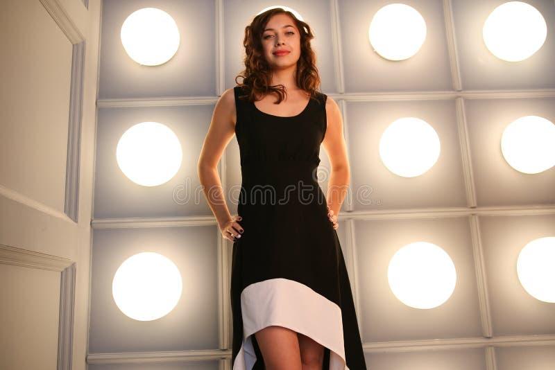 Immagine la ragazza in un vestito nero in integrale fotografia stock