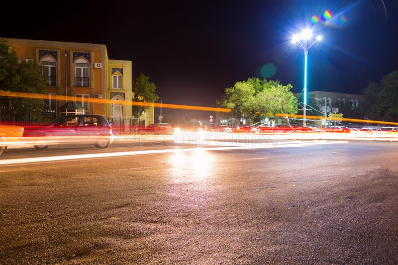 Immagine lunga di esposizione delle automobili che precipitano sopra una strada principale nel centro della città di Buchara, l'U immagine stock libera da diritti