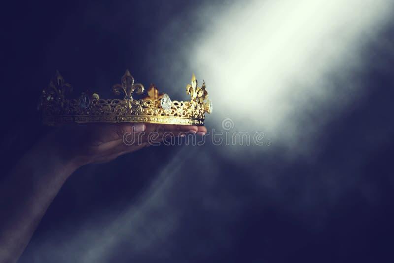 Immagine magica di Mysteriousand della mano del ` s della donna che tiene una corona dell'oro sopra fondo nero gotico concetto me fotografie stock libere da diritti