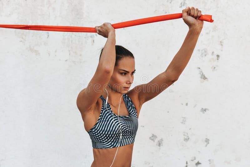 Immagine orizzontale della condizione graziosa del corridore della donna contro il muro di cemento che fa allungando gli esercizi immagine stock