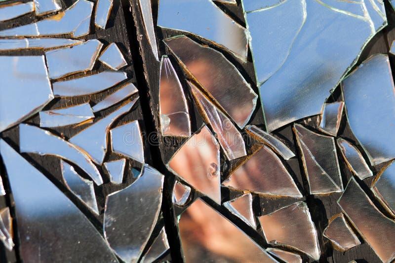 Immagine oscurata di una donna nella riflessione di vetro rotta fotografia stock libera da diritti
