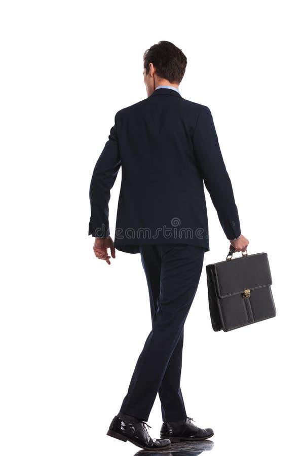 Immagine posteriore di vista di un uomo di affari che cammina con la cartella fotografie stock libere da diritti