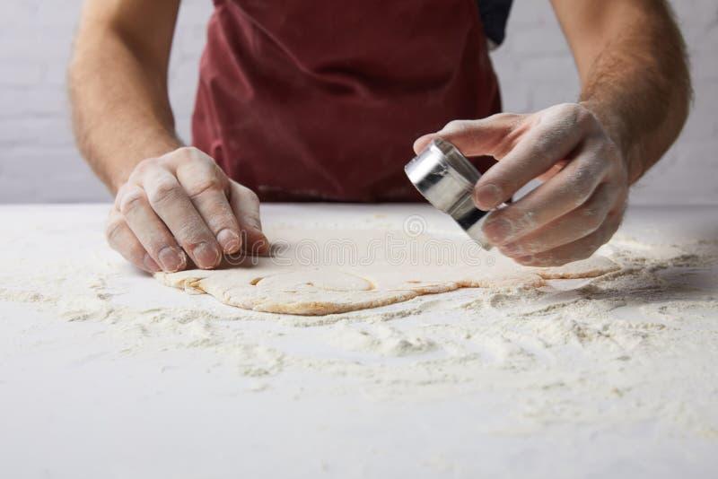 Immagine potata del cuoco unico che prepara i biscotti a forma di cuore con la muffa della pasta fotografia stock libera da diritti