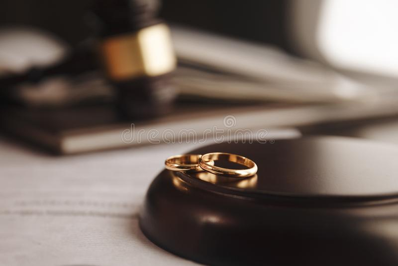 Immagine potata del giudice di divorzio che colpisce martelletto sugli anelli dorati allo scrittorio in aula di tribunale immagini stock