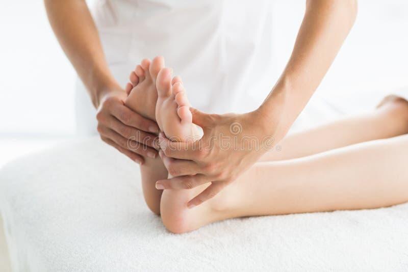 Immagine potata del massaggiatore che dà massaggio del piede alla donna fotografia stock libera da diritti