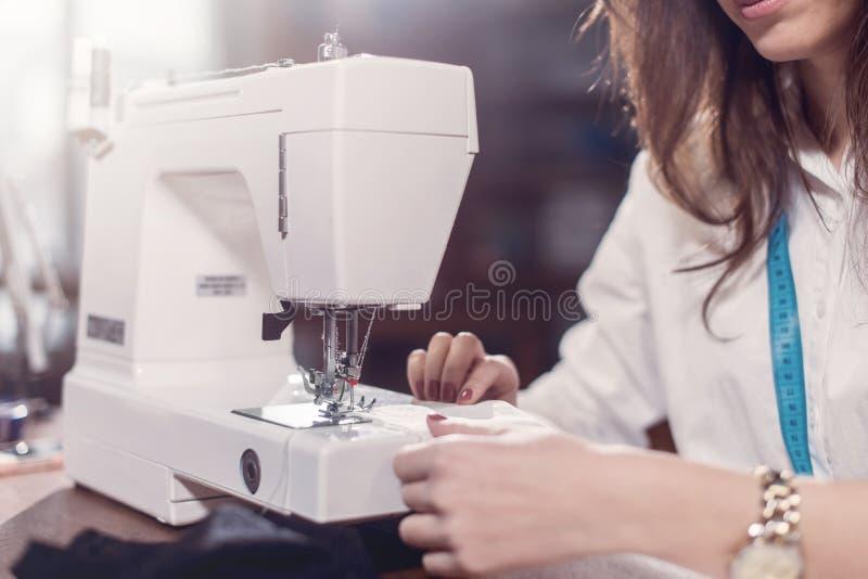 Immagine potata del sarto femminile che cuce pizzo fine con la macchina per cucire che si siede nello studio di sartoria fotografie stock libere da diritti