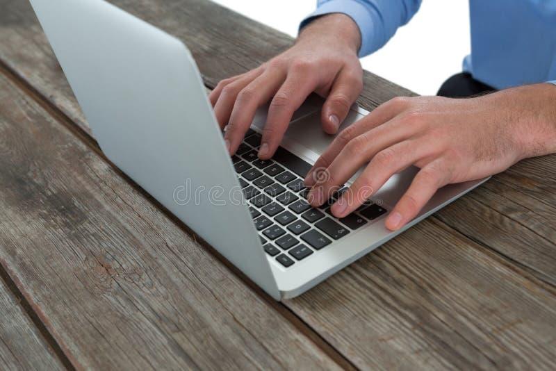 Immagine potata dell'uomo d'affari facendo uso del computer portatile alla tavola di legno fotografia stock libera da diritti