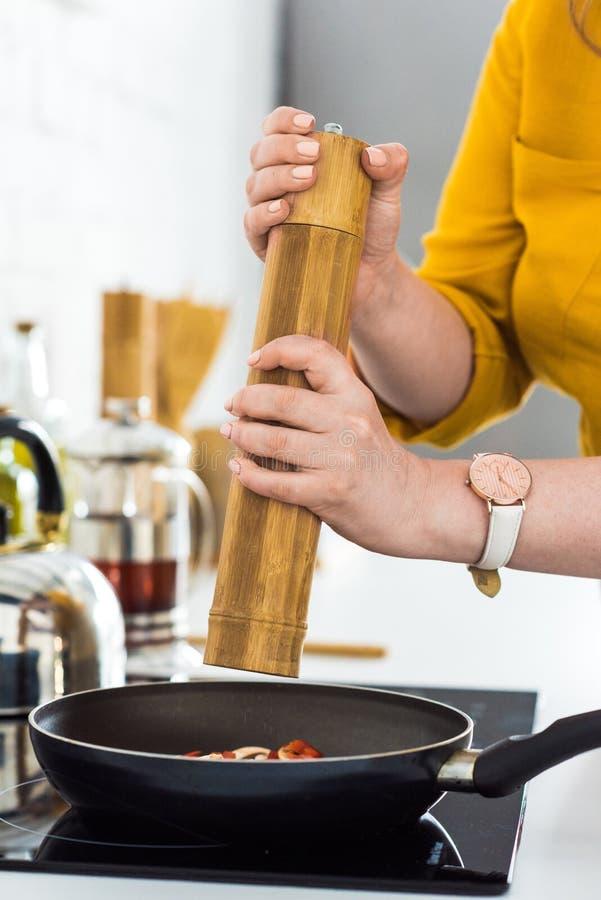 immagine potata della donna che aggiunge le spezie a friggere le verdure fotografie stock
