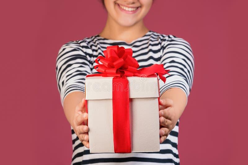 Immagine potata della ragazza con il contenitore di regalo isolato sopra fondo rosa immagine stock