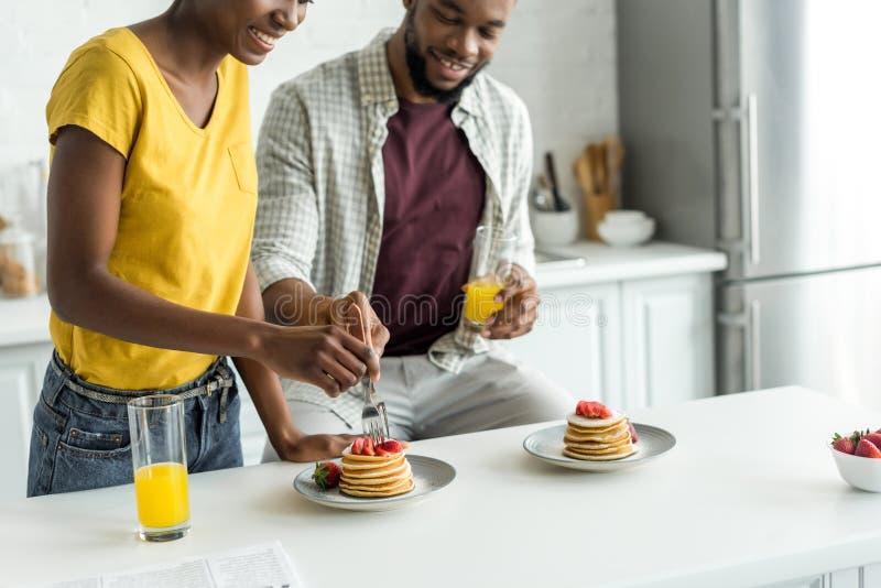 immagine potata delle coppie afroamericane che mangiano i pancake e che bevono succo d'arancia fotografia stock