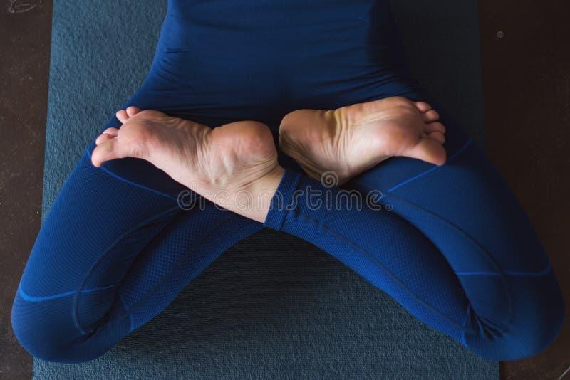 Immagine potata delle gambe femminili che si trovano nella posa di yoga del loto sulla stuoia all'interno fotografia stock