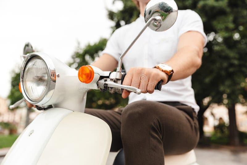 Immagine potata di giovane guida dell'uomo di affari sul motorino retro fotografie stock