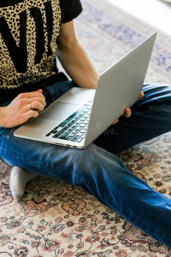 Immagine potata di un giovane che lavora al computer che si siede alla tavola di legno immagini stock
