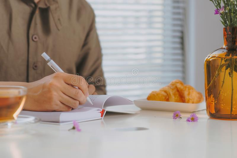 Immagine potata di un uomo che si siede alla tavola di legno bianca d'annata e fotografie stock