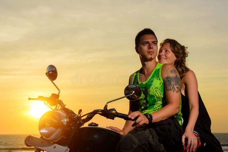 Immagine romantica con una coppia di bei motociclisti alla moda al tramonto Il tipo bello con il tatoo e la giovane donna sexy go immagini stock libere da diritti