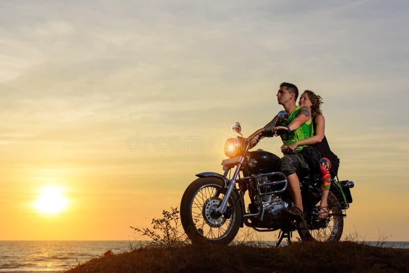 Immagine romantica con una coppia di bei motociclisti alla moda al tramonto Tipo bello con il tatoo e giovane donna sexy fotografia stock libera da diritti