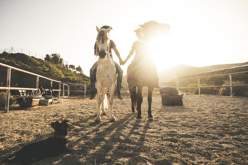 Immagine scenica di equitazione con due coppie della gente ed animali e un cane che prende le mani con luce solare di amore e di  fotografia stock