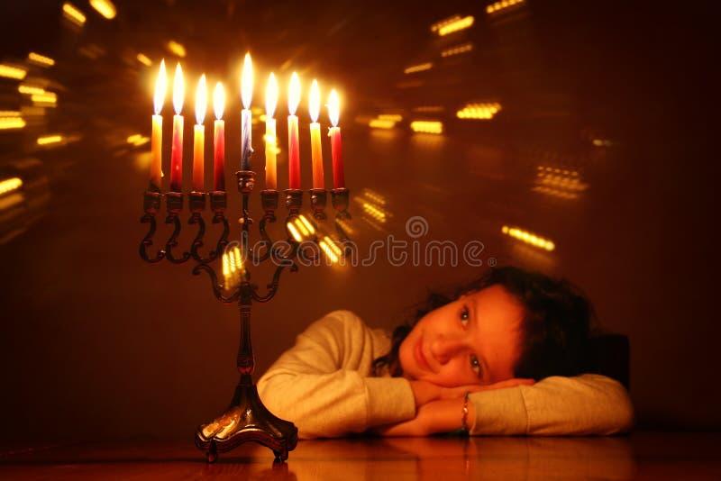 Immagine scura del fondo ebreo di Chanukah di festa con la ragazza sveglia che esamina menorah & x28; candelabra& tradizionale x2 immagine stock