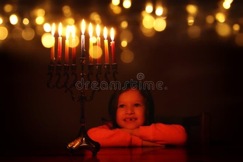 Immagine scura del fondo ebreo di Chanukah di festa con la ragazza sveglia che esamina menorah & x28; candelabra& tradizionale x2 fotografia stock libera da diritti