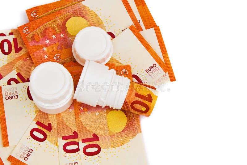 Immagine simbolica per alto costo di medicina con la bottiglia di pillola fotografie stock