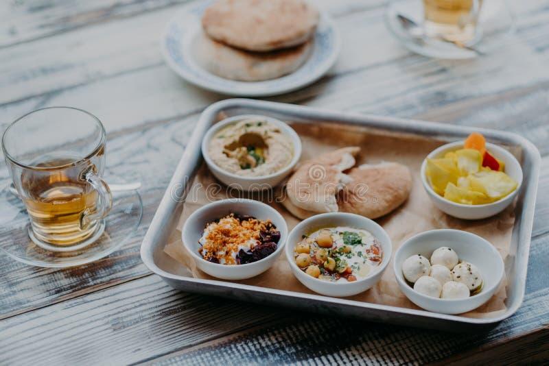 Immagine sopraelevata dell'alimento tradizionale di Israele sul vassoio Hummus, formaggio di capra domestica, il centro del tomat fotografie stock libere da diritti