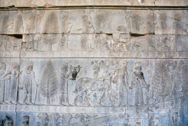 Immagine storica di vita della gente antica su grande bassorilievo di pietra in Persepolis, Iran fotografia stock libera da diritti
