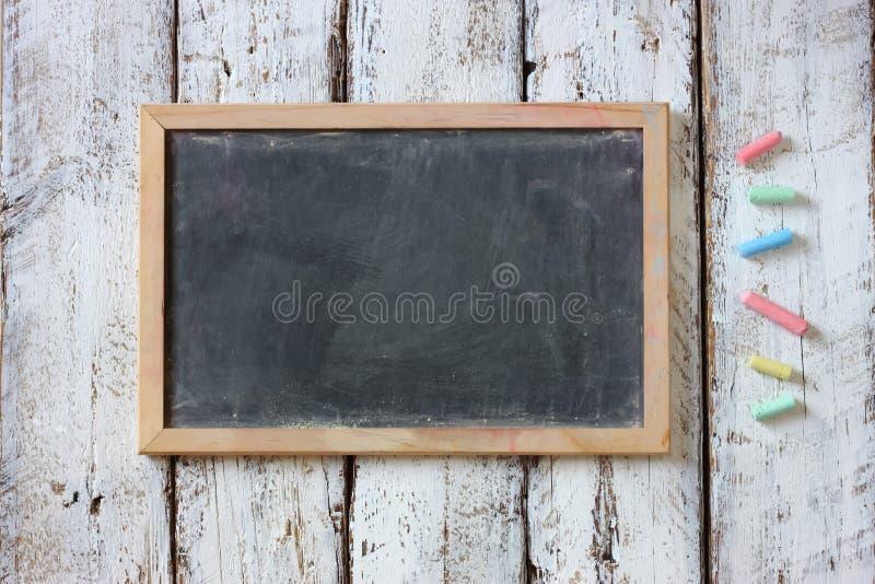 Immagine superiore della lavagna e dei gessi variopinti sopra la tavola di legno fotografia stock libera da diritti