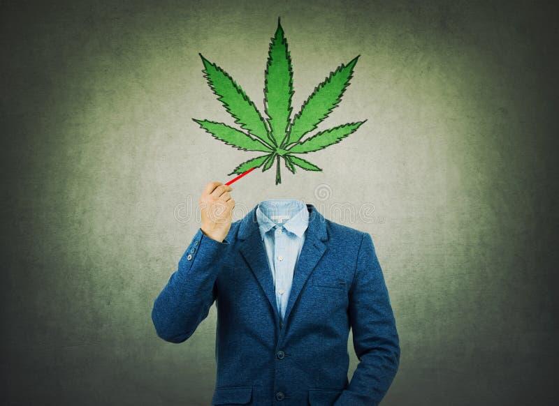 Immagine surreale come uomo d'affari con il fronte invisibile che tiene una matita nel suo simbolo della foglia della marijuana d immagine stock libera da diritti