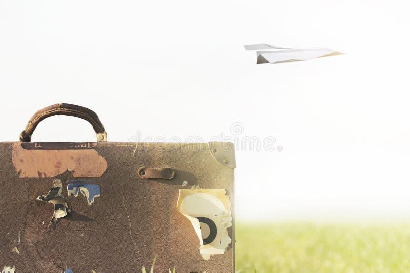Immagine surreale di un aeroplano di carta che sorvola una valigia immagini stock