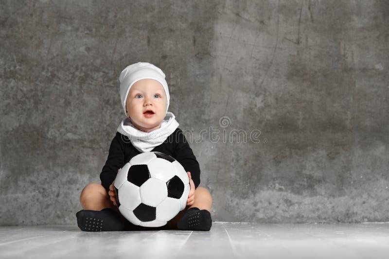 Immagine sveglia del bambino che tiene un pallone da calcio fotografie stock