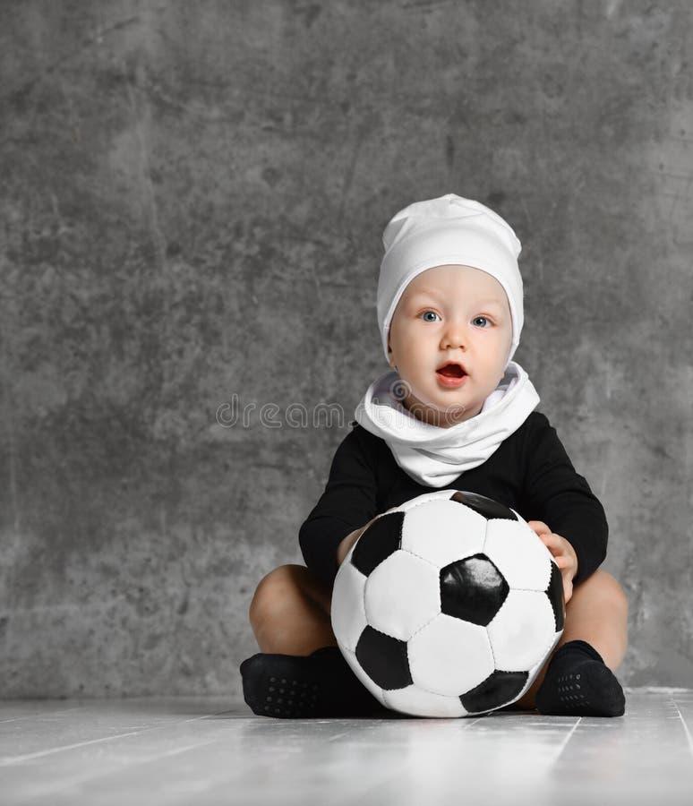 Immagine sveglia del bambino che tiene un pallone da calcio fotografia stock libera da diritti