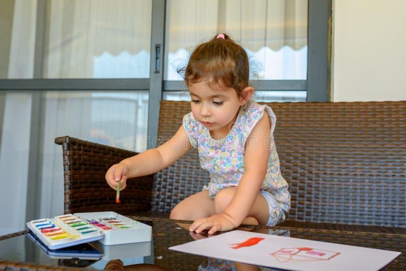 Immagine sveglia della pittura della bambina su fondo interno domestico Ragazzo e ragazze che si siedono sullo scrittorio pratica immagini stock libere da diritti