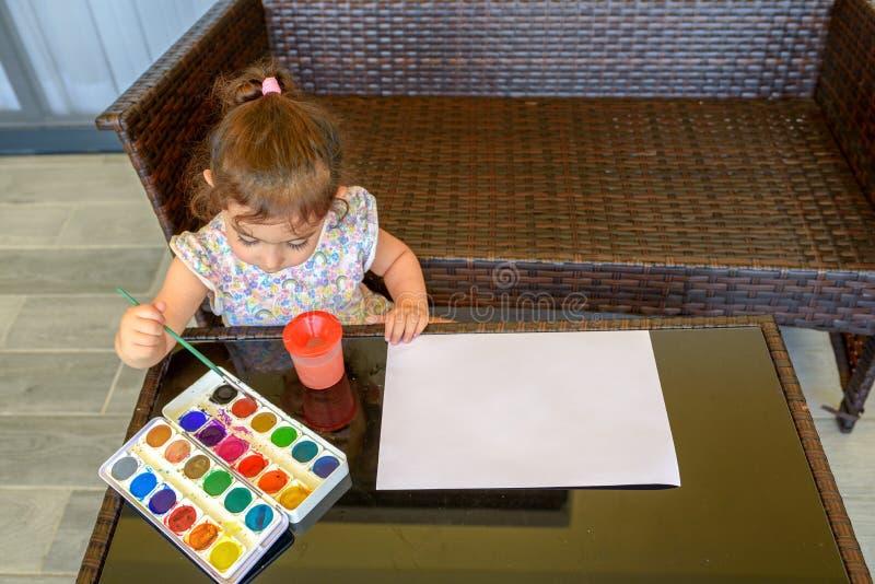 Immagine sveglia della pittura della bambina su fondo interno domestico Ragazzo e ragazze che si siedono sullo scrittorio pratica immagine stock libera da diritti