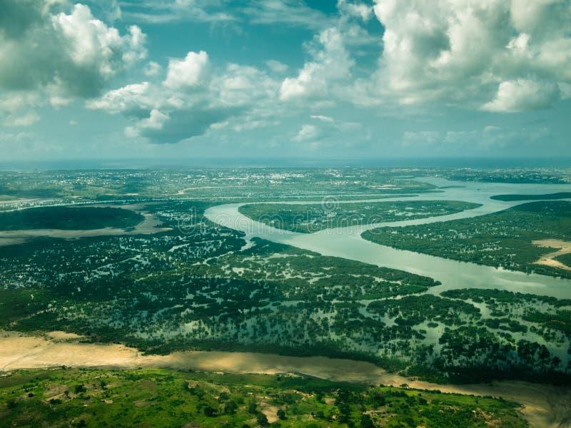 Immagine tonificata dalla finestra di un aeroplano della foresta della zona umida e del fiume con la città di Mombasa nei precede immagini stock