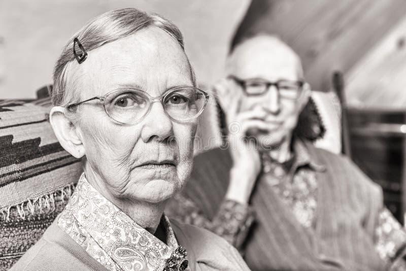 Immagine tonificata delle coppie anziane che si siedono nel salone immagini stock libere da diritti