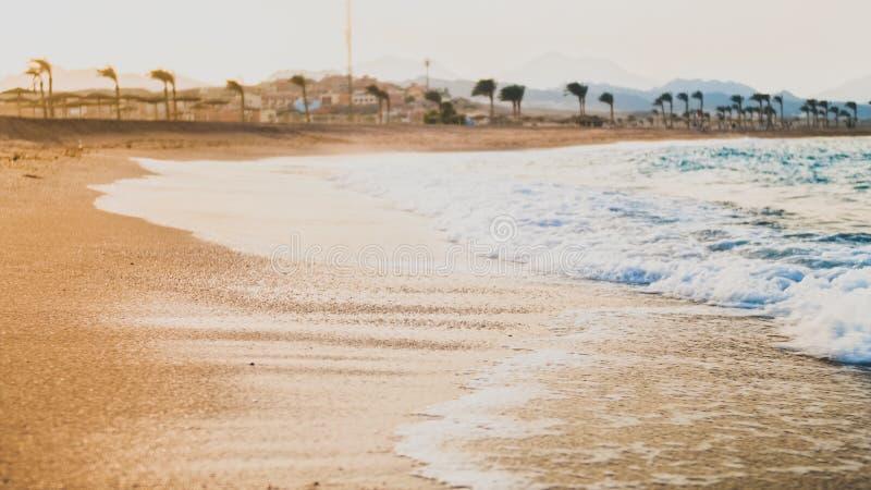 Immagine tonificata primo piano di susnet di stupore sopra la spiaggia sabbiosa del mare e le onde blu di rotolamento del mare r fotografia stock libera da diritti