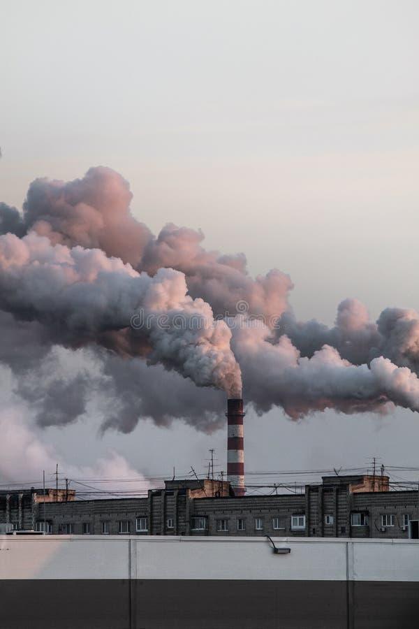 Immagine verticale dei camini industriali con fumo pesante che causa inquinamento atmosferico fotografia stock