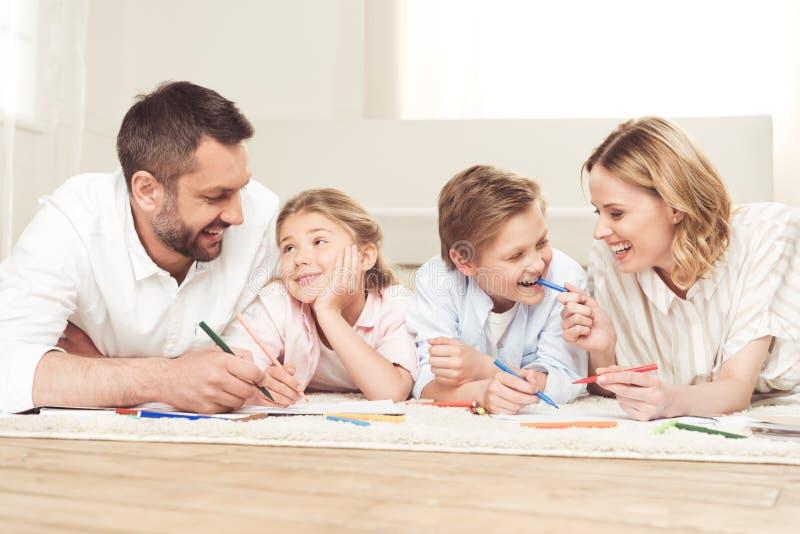 Immagini del disegno della famiglia mentre trovandosi sul pavimento a casa immagini stock libere da diritti