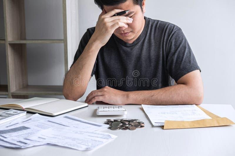 Immagini del marito sollecitato che utilizza calcolatore a calcolare le fatture della ricevuta di spesa di vari costo e spese di  fotografie stock