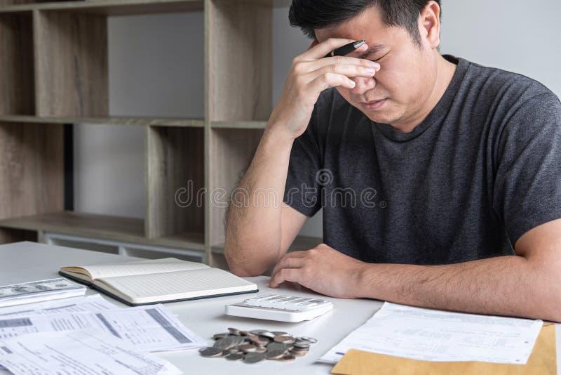 Immagini del marito sollecitato che utilizza calcolatore a calcolare le fatture della ricevuta di spesa di vari costo e spese di  fotografia stock