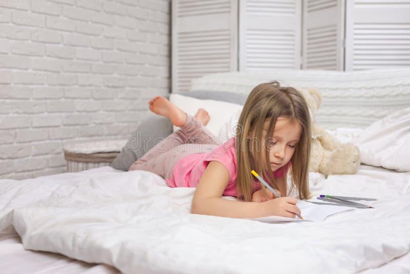 Immagini di disegno della bambina sveglia mentre trovandosi sul letto immagini stock