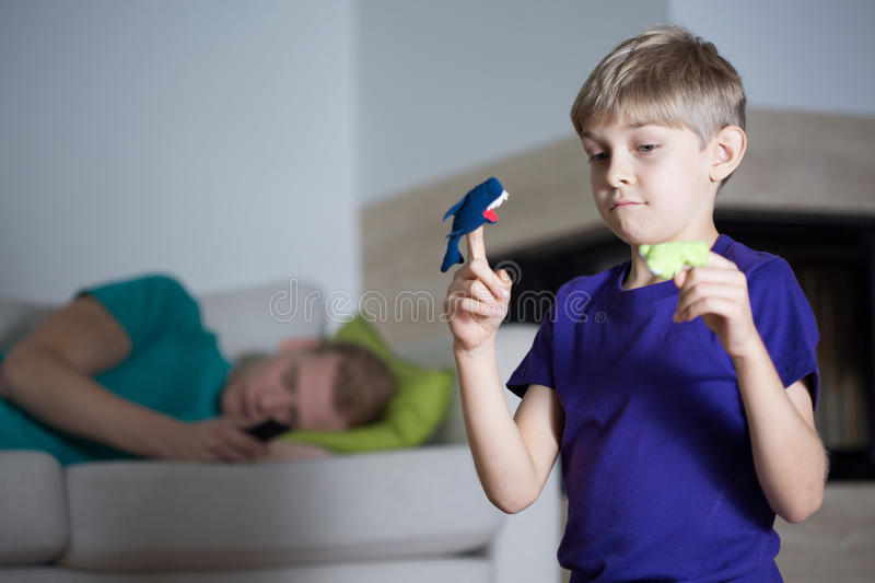 Immature dad is sleeping. During his son playing alone royalty free stock photo