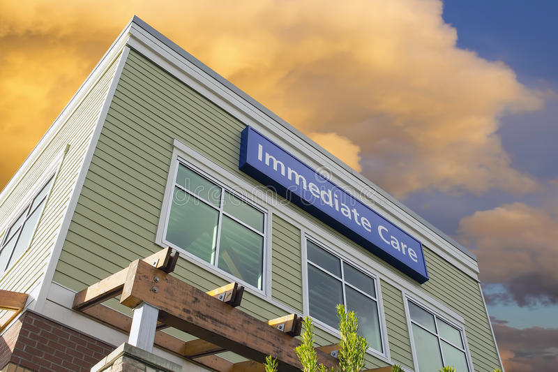 Immediate Care Sign On Hospital Building with Clouds. Immediate Care Sign Above Windows Outside Hospital or Emergency Clinic Building Against Sky with Clouds royalty free stock photography