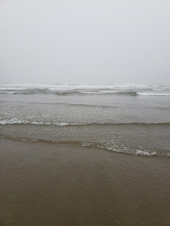 Immer regnende Oregon-Küste, weil das Land nie zurück zu dem Meer wellenartig bewegt stockfotografie