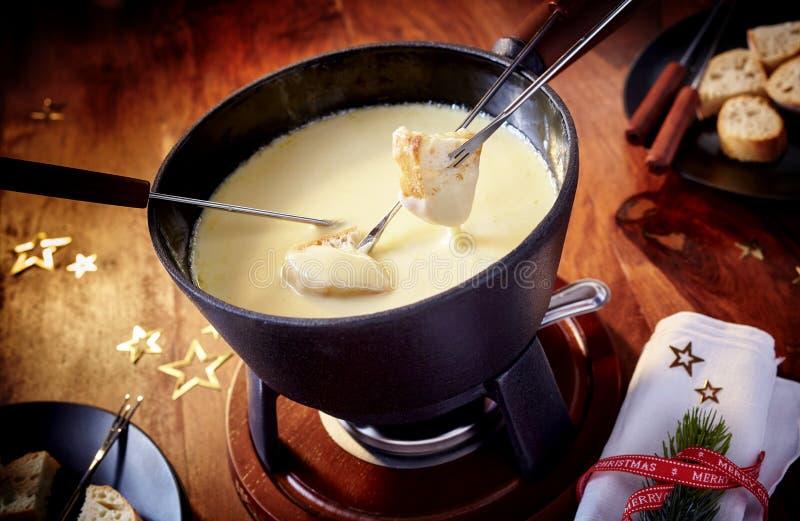 Immergendo pane in una fonduta di formaggio deliziosa immagini stock libere da diritti