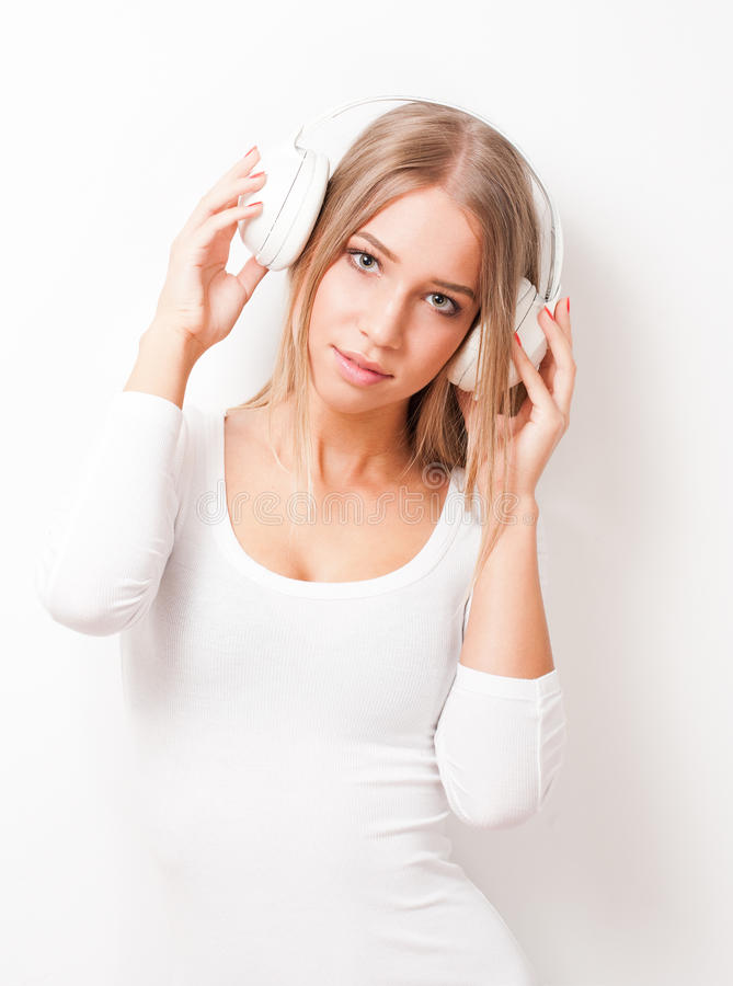 Immersed in music. Portrait of blond beauty listening to music in white headphones royalty free stock photos